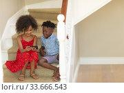 Купить «Mixed race girl and her younger brother using phone at home», фото № 33666543, снято 28 ноября 2019 г. (c) Wavebreak Media / Фотобанк Лори