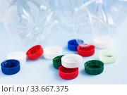 Купить «Colorful plastic caps against bottles. Plastic wrapping rubbish on blue background. Concept of environmental pollution», фото № 33667375, снято 30 апреля 2020 г. (c) Papoyan Irina / Фотобанк Лори