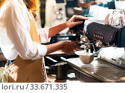 Купить «Close-up shot of a barista brewing coffee by modern coffeemaker machine to making a cup of coffee with other barista working in background. Using for small business entrepreneur owner concept.», фото № 33671335, снято 10 июля 2020 г. (c) easy Fotostock / Фотобанк Лори