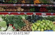 Купить «Large assortment of fresh colorful fruits and vegetables in wicker trays on shelves in supermarket», видеоролик № 33672967, снято 20 ноября 2019 г. (c) Яков Филимонов / Фотобанк Лори