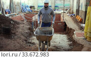 Купить «Young bearded man working at building site, carrying navvy wheelbarrow with bucket of construction mortar», видеоролик № 33672983, снято 29 мая 2020 г. (c) Яков Филимонов / Фотобанк Лори