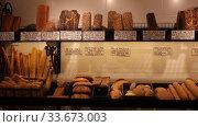 Купить «Variety of freshly baked bread, baguettes and buns on shelves in bakery shop. Price tags in Catalan with names of bakery products», видеоролик № 33673003, снято 5 февраля 2020 г. (c) Яков Филимонов / Фотобанк Лори