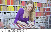 Купить «Stylish young woman choosing color of hair dye from palette in shop», видеоролик № 33673011, снято 4 июня 2020 г. (c) Яков Филимонов / Фотобанк Лори