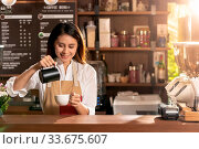 Купить «Young adult asian female barista pouring fresh milk to prepare latte coffee for customer in cafe bar.», фото № 33675607, снято 10 июля 2020 г. (c) easy Fotostock / Фотобанк Лори