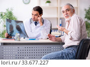 Купить «Young male doctor and old patient in antismoking concept», фото № 33677227, снято 9 сентября 2019 г. (c) Elnur / Фотобанк Лори