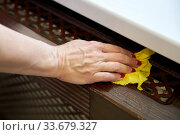 Woman wipes a window sill with a damp yellow rag. Стоковое фото, фотограф Олег Белов / Фотобанк Лори