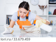 Купить «Young woman wearing uniform cleaning table at office», фото № 33679459, снято 18 апреля 2018 г. (c) Яков Филимонов / Фотобанк Лори
