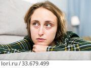 Купить «Portrait of sorrowful woman sitting at home», фото № 33679499, снято 6 ноября 2018 г. (c) Яков Филимонов / Фотобанк Лори