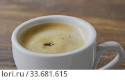 Купить «Close-up of coffee splashes fall into a cup of espresso with froth on a brown wooden table. Slow motion, Full HD video, 240fps, 1080p.», видеоролик № 33681615, снято 31 августа 2018 г. (c) Ярослав Данильченко / Фотобанк Лори