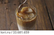 Hand mixes fresh cold coffee drink with spoon on a wooden background. Стоковое видео, видеограф Ярослав Данильченко / Фотобанк Лори