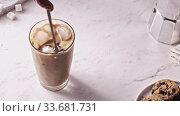 Купить «Mixing freshly prepared ice coffee drink with milk by spoon.», видеоролик № 33681731, снято 18 марта 2019 г. (c) Ярослав Данильченко / Фотобанк Лори