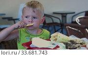 A funny four-year-old boy enjoys eating a burger in a cafe. Стоковое видео, видеограф Aleksandr Lutcenko / Фотобанк Лори