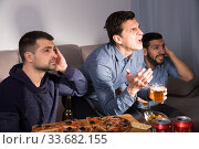 Males in suspense watching tv with beer and pizza. Стоковое фото, фотограф Яков Филимонов / Фотобанк Лори
