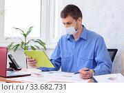 Офисный сотрудник общается в планшете по видеосвязи, на лице медицинская маска. Стоковое фото, фотограф Иванов Алексей / Фотобанк Лори