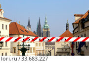 Coronavirus in Prague, Czech Republic. St. Vitus Cathedral (Roman Catholic cathedral ). Covid-19 sign on a blurred background. Concept of COVID pandemic and travel in Europe. (2019 год). Стоковое фото, фотограф Владимир Журавлев / Фотобанк Лори
