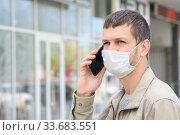 Портрет мужчины в маске с мобильным телефоном на фоне магазина. Стоковое фото, фотограф Иванов Алексей / Фотобанк Лори