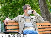 Мужчина в защитной маске прогуливается по парку и присев на лавочку разговаривает по телефону. Стоковое фото, фотограф Иванов Алексей / Фотобанк Лори