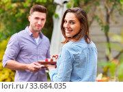 Junge Frau und ihr Freund essen einen Snack auf einer Party oder auf Sommerfest. Стоковое фото, фотограф Zoonar.com/Robert Kneschke / age Fotostock / Фотобанк Лори