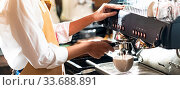 Купить «Close-up shot of a barista brewing coffee by modern coffeemaker machine to making a cup of coffee with other barista working. Using for small business entrepreneur owner, Panorama web banner crop.», фото № 33688891, снято 10 июля 2020 г. (c) easy Fotostock / Фотобанк Лори
