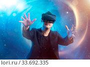 Купить «The young man wearing virtual reality goggles with amazing cosmic futuristic space virtual imaging background.», фото № 33692335, снято 27 мая 2020 г. (c) easy Fotostock / Фотобанк Лори