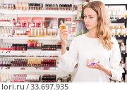 Купить «Woman choosing perfume in cosmetics store», фото № 33697935, снято 19 октября 2019 г. (c) Яков Филимонов / Фотобанк Лори