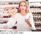 Купить «Woman applying powder in cosmetics store», фото № 33697943, снято 19 октября 2019 г. (c) Яков Филимонов / Фотобанк Лори