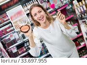 Купить «Portrait of attractive girl demonstrating powder in makeup store», фото № 33697955, снято 19 октября 2019 г. (c) Яков Филимонов / Фотобанк Лори