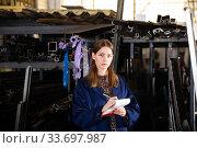 Купить «Young female standing with notepad in production workshop», фото № 33697987, снято 12 июля 2020 г. (c) Яков Филимонов / Фотобанк Лори