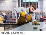 Professional worker drills hole in metal plate with screwdriver. Стоковое фото, фотограф Яков Филимонов / Фотобанк Лори