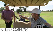 Caucasian male golfers into a golf buggy . Стоковое видео, агентство Wavebreak Media / Фотобанк Лори