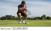 Caucasian male golfer kneeling on a golf course on a sunny day. Стоковое видео, агентство Wavebreak Media / Фотобанк Лори