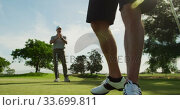 Caucasian male golfer reaching down a ball out of the hole on a golf course on a sunny day. Стоковое видео, агентство Wavebreak Media / Фотобанк Лори