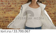 Купить « Caucasian woman showing her outfit on a brick wall», видеоролик № 33700067, снято 23 июля 2019 г. (c) Wavebreak Media / Фотобанк Лори