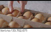 Купить «Close-up view girl's hand takes one egg from paper container. Slow motion, Full HD video, 240fps, 1080p. Process preparing of homemade bake.», видеоролик № 33702071, снято 31 августа 2018 г. (c) Ярослав Данильченко / Фотобанк Лори