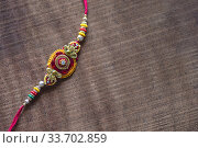 Raksha Bandhan background with an elegant Rakhi. A traditional Indian wrist band which is a symbol of love between Brothers and Sisters. Стоковое фото, фотограф Dipak Chhagan Shelare / easy Fotostock / Фотобанк Лори