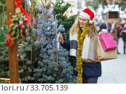 Купить «Girl with paper bags choosing Christmas tree», фото № 33705139, снято 20 декабря 2018 г. (c) Яков Филимонов / Фотобанк Лори