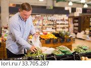 Купить «Man choosing green beans at grocery store», фото № 33705287, снято 9 октября 2019 г. (c) Яков Филимонов / Фотобанк Лори
