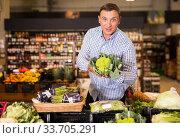 Купить «Customer buying cauliflower at supermarket», фото № 33705291, снято 9 октября 2019 г. (c) Яков Филимонов / Фотобанк Лори