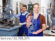 Купить «Female worker demonstrating drilled glass», фото № 33705371, снято 10 сентября 2018 г. (c) Яков Филимонов / Фотобанк Лори