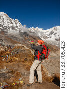Купить «Young woman with backpack takes photo of mountain landscape, Annapurna Base Camp, Nepal», фото № 33705423, снято 8 октября 2012 г. (c) Юлия Бабкина / Фотобанк Лори