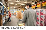 Купить «Young man in protective mask walking between sections in the big grocery shop», фото № 33705507, снято 3 июля 2020 г. (c) Константин Шишкин / Фотобанк Лори