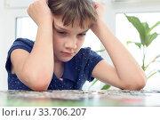 Купить «Девочка думает над головоломкой сидя дома за столом», фото № 33706207, снято 4 мая 2020 г. (c) Иванов Алексей / Фотобанк Лори