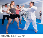 Adults are practicing new karate moves in pairs. Стоковое фото, фотограф Яков Филимонов / Фотобанк Лори