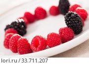 Купить «raspberries and blackberries laid out on a white plate in circle», фото № 33711207, снято 2 июня 2019 г. (c) Татьяна Яцевич / Фотобанк Лори