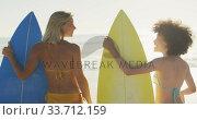 Купить «Women holding their surfboards behind the sea», видеоролик № 33712159, снято 25 февраля 2020 г. (c) Wavebreak Media / Фотобанк Лори