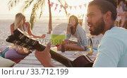 Купить «Friends enjoying a party on the beach », видеоролик № 33712199, снято 25 февраля 2020 г. (c) Wavebreak Media / Фотобанк Лори