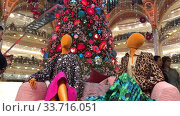 PARIS, FRANCE - DECEMBER 19, 2019: Mannequins on the background of the Christmas tree in the scenery in the gallery Lafayette. Редакционное видео, видеограф Ирина Аринина / Фотобанк Лори