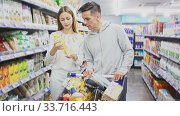 Portrait of young man and woman with shopping cart in supermarket. Стоковое видео, видеограф Яков Филимонов / Фотобанк Лори