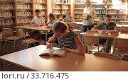Купить «Teenage pupils sitting at table and studying, teacher in classroom», видеоролик № 33716475, снято 24 сентября 2019 г. (c) Яков Филимонов / Фотобанк Лори