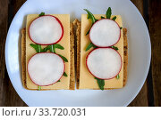 Sandwich made from rye bread, hard cheese, radish, arugula, served on a white plate against a dark wooden background. Symmetry. Copy space. Flat lay, top view. Close-up. Стоковое фото, фотограф Tetiana Chugunova / Фотобанк Лори